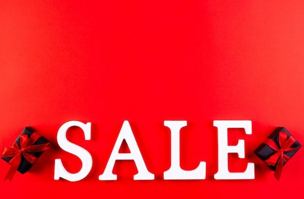 Деревянные текстовые слова продажа с копией пространства на красном.