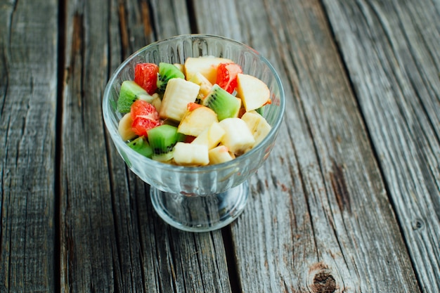 The wooden texture is salad in a glass container of different fruits