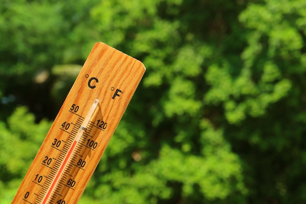 Wooden thermometer in the summer sunlight showing high temperature