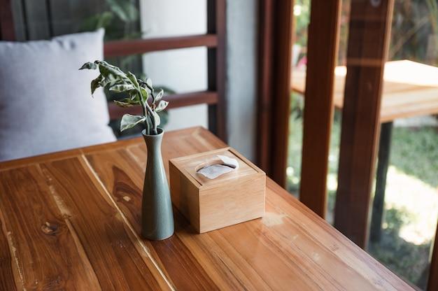 Деревянная коробка для салфеток с растением в керамической вазе на деревянном столе в гостиной