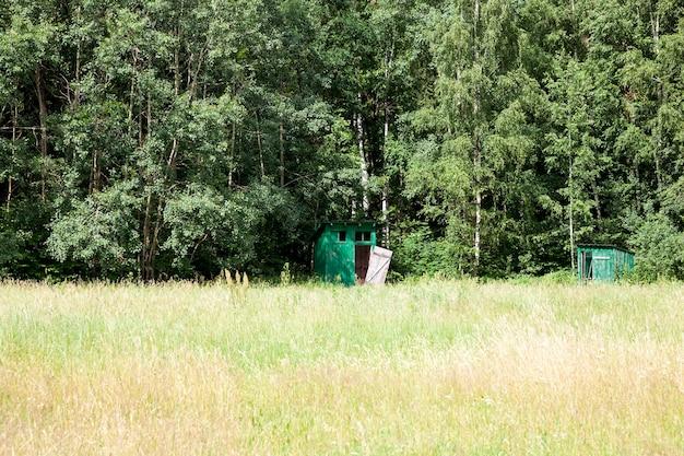 森の近くの木製トイレ