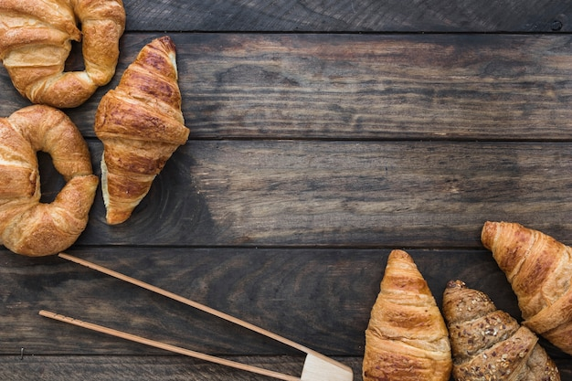 Wooden tongs near croissants