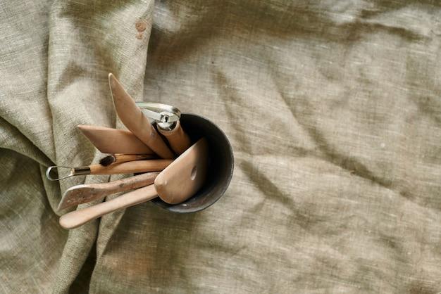 세라믹 유리의 린넨 배경에 점토와 도자기로 작업하기 위한 나무 도구