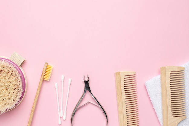 Wooden toothbrush, comb and nippers on pink