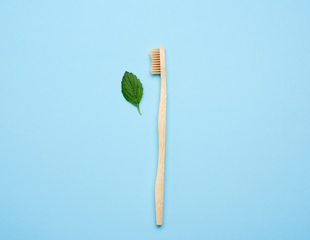Деревянная зубная щетка на синем фоне, концепция отбраковки пластика, ноль отходов, плоская планировка