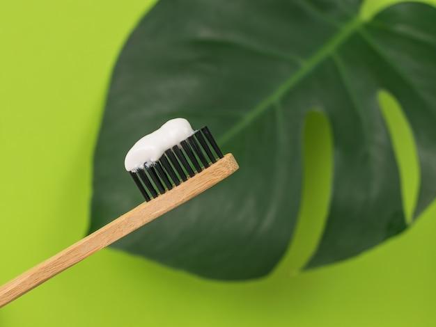 モンステラの葉の背景に木製の歯ブラシ。