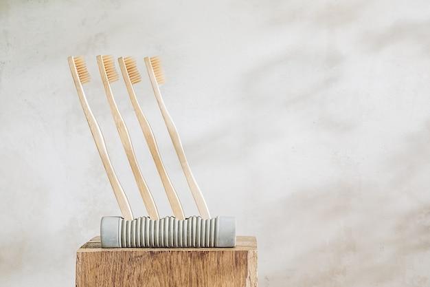 Деревянные зубные щетки в бетонной подставке на светлом мраморном фоне