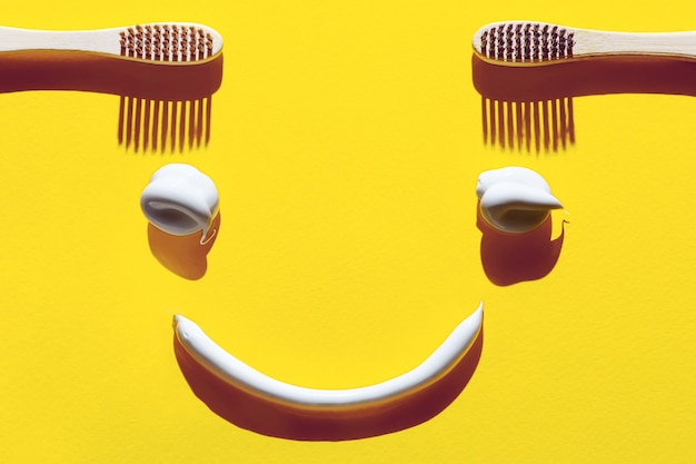 Wooden toothbrushes and pasta on a yellow background. dental concept in the form of a funny face.