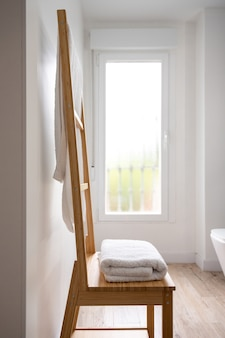 Wooden towel rack in a bright modern bathroom