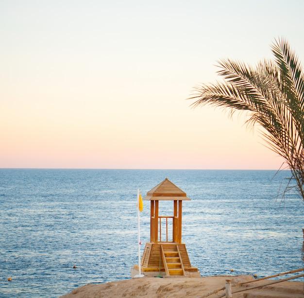 日没時の熱帯の海のライフガードの木製タワー