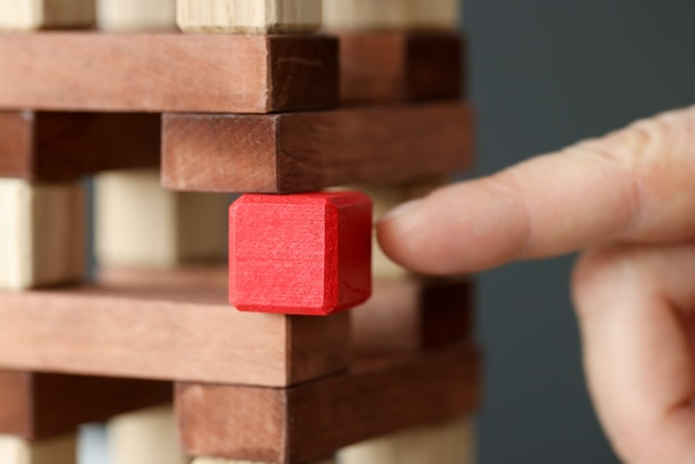 Wooden tower made of wooden brown cubes from which red cube is taken. unique business commercial proposal concept
