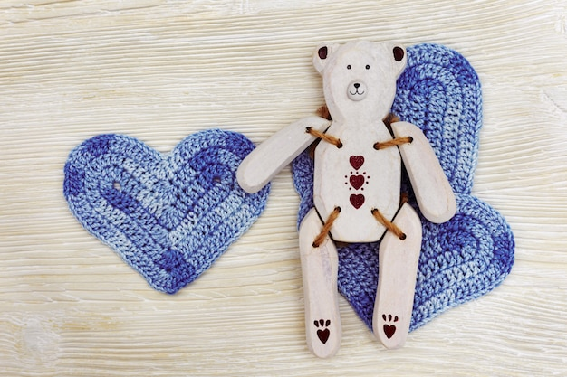 Wooden toy-bear with blue knitted heart. handmade white wooden toy bear on white wood background.