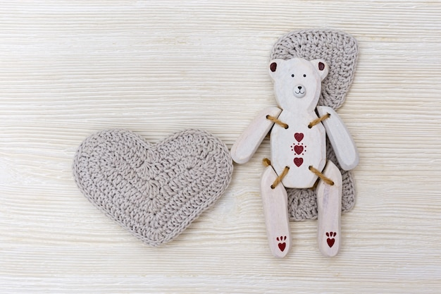 Wooden toy-bear with heart. white wooden bear on wood