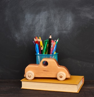 Wooden toy, book, multicolored pens and pencils