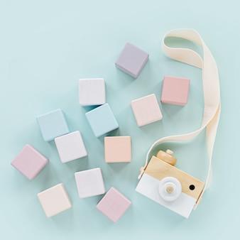 나무 장난감 카메라와 다채로운 장난감 블록. 밝은 파란색 배경에 세련된 아기 장난감입니다. 어린이를 위한 친환경 플라스틱 무료 장난감 액세서리. 평평한 평지, 평면도