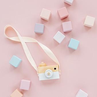 나무 장난감 카메라와 다채로운 장난감 블록. 파스텔 핑크 배경에 세련된 아기 장난감. 어린이를 위한 친환경 플라스틱 무료 장난감 액세서리. 평평한 평지, 평면도