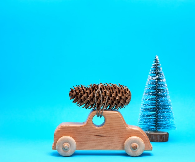 Wooden toy car carries on top a pine cone