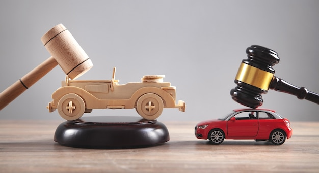 Wooden toy car, red car and judge gavels.
