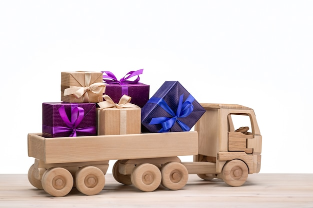 Деревянная игрушечная машинка. грузовик с подарками в красочных коробках.