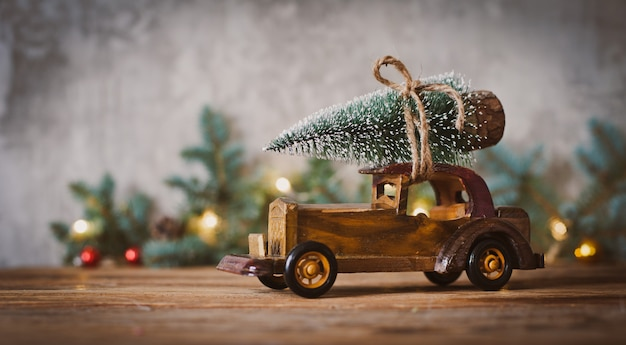 Wooden toy car with christmas tree on the roof on a wooden table.