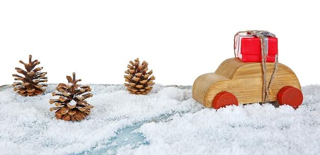 눈 덮인 테이블에 선물 상자와 콘이 있는 나무 장난감 자동차