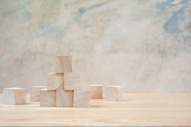 木製のテーブルang灰色の背景上の木のおもちゃのキューブ