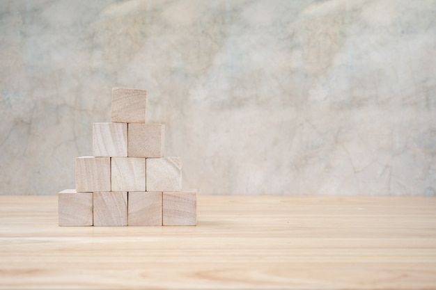 Wooden toy cubes on wooden table ang grey background