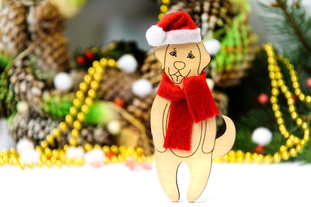 A wooden toy dog in a christmas hat