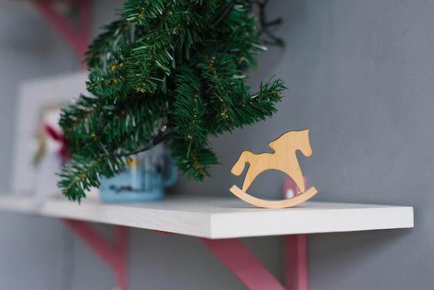 Деревянная игрушка лошадь из фанеры находится на полке в комнате