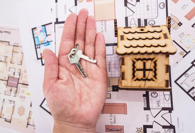 木のおもちゃの家と手のひらの鍵。家を改築、購入、または建てるという概念。