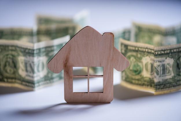 木のおもちゃの家と白い背景の上のお金