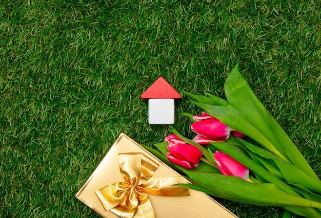 나무로되는 장난감 집과 푸른 잔디에 선물 상자와 튤립