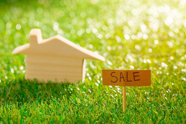 Wooden toy house on grass with sale sign close up