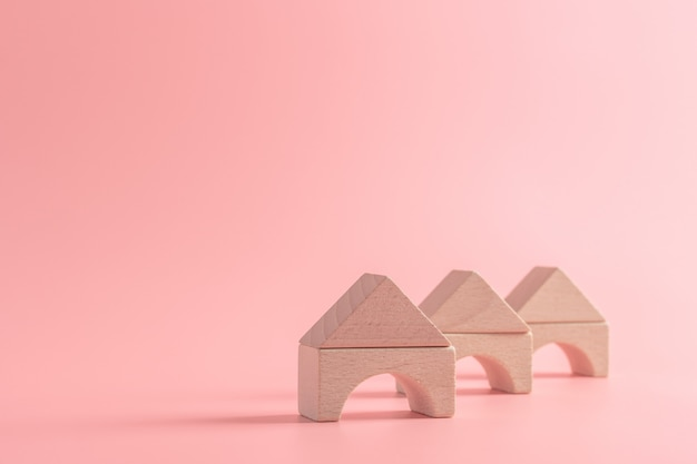 Wooden toy house or home on isolated pink. property living insurance, create family dream concept
