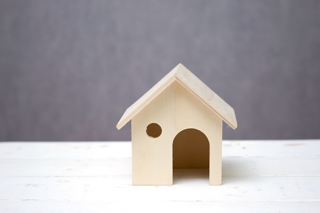 Wooden toy house or home on white table gray background.