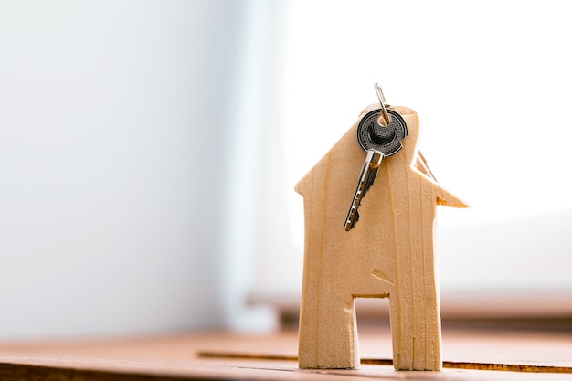 Wooden toy house and house keys close up. real estate concept
