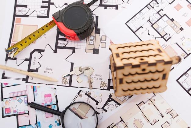 木のおもちゃの家、巻尺の付いた鍵、家の計画にある虫眼鏡。