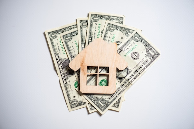 Wooden toy house and money on a white background