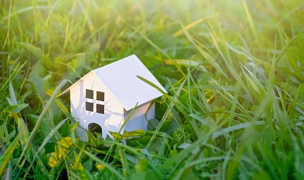 Деревянный игрушечный домик на фоне зеленой травы