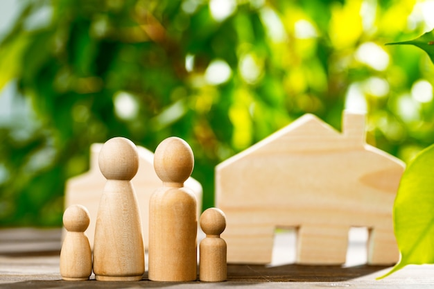 Wooden toy house and wooden family on foliage background close up