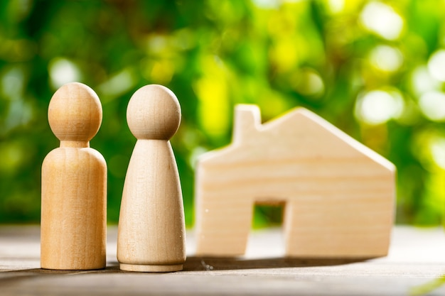 Wooden toy house and wooden family on foliage close up