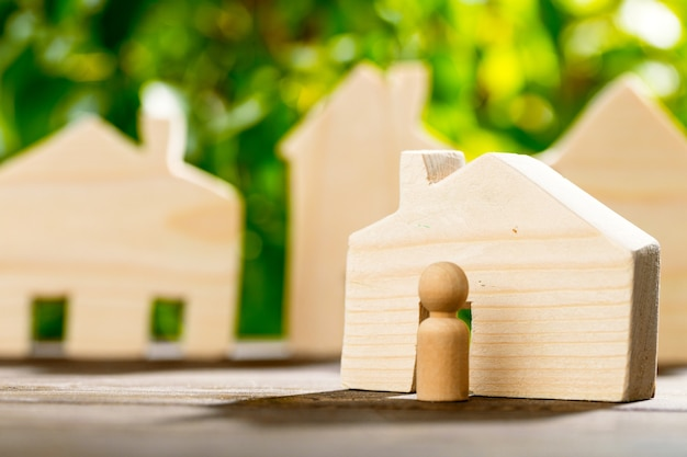 Wooden toy house and wooden family on foliage surface