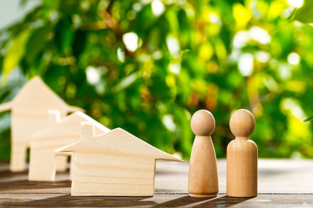 Wooden toy house and wooden family on foliage