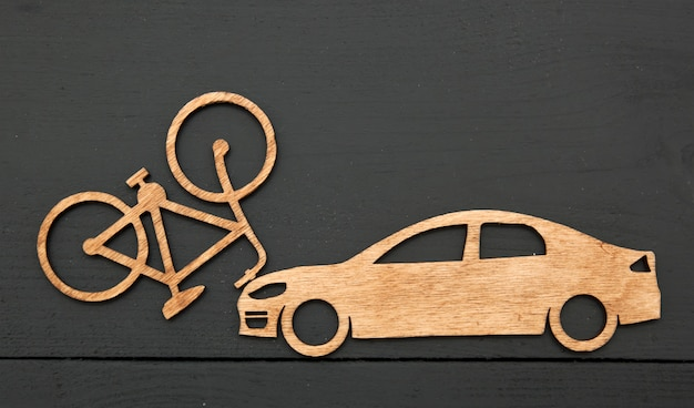 木のおもちゃの小さな車と石の背景に自転車。サイクリストとのコンセプトカー事故