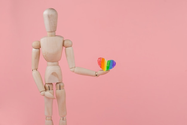 Wooden toy man with a rainbow paper heart