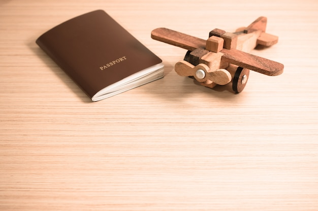 Wooden toy plane and the passport with copy space. travel concept
