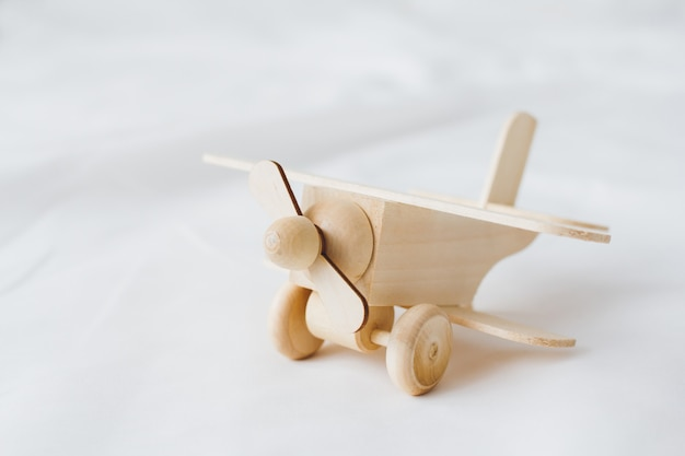 Wooden toy plane stands on a white background