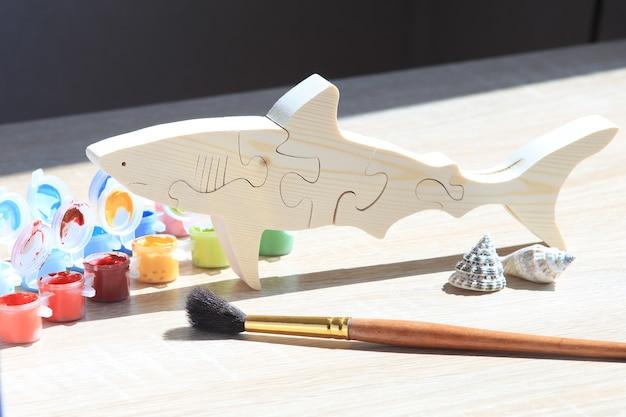 Деревянная игрушка-головоломка в форме животного и цветная краска на фоне текстуры древесины