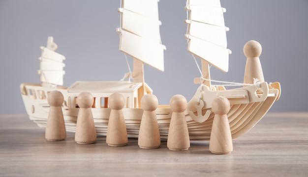 木のおもちゃの船と人間の木のフィギュア。リーダー。チームワーク。パートナーシップ。人材