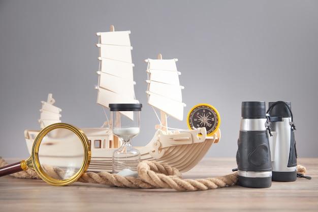 나무 장난감 배, 나침반, 로프, 쌍안경, 돋보기, 모래 시계. 여행